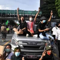 Pro-democracy protesters give the three-finger salute while sitting on a police vehicle during a rally at a traffic intersection in Bangkok on Thursday.  | AFP-JIJI
