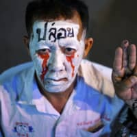 A man shows the three-finger salute during a gathering of pro-democracy protesters in Bangkok on Thursday.  | REUTERS