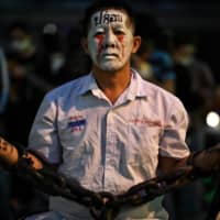 A pro-democracy protester wears chains and make-up during a demonstration at an intersection in Bangkok on Thursday  | AFP-JIJI