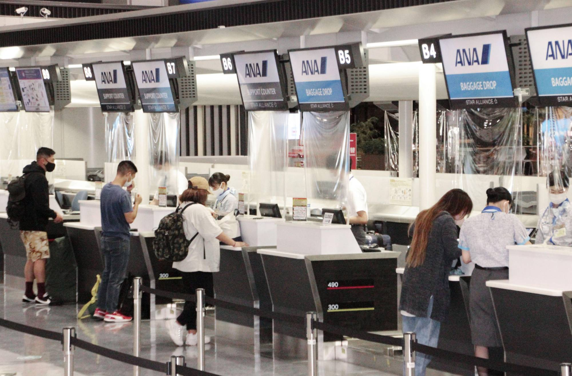 People traveling abroad check in at airline counters at Narita airport on Oct. 5.  | KYODO
