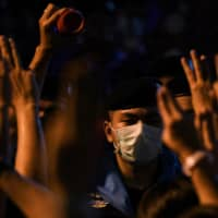 People show the three-finger salute to police officers during a gathering of pro-democracy protesters on Thursday in Bangkok.  | REUTERS