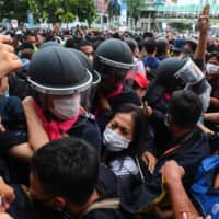 Pro-democracy protesters scuffle with the police as another gives the three-finger salute in Bangkok on Thursday.  | AFP-JIJI