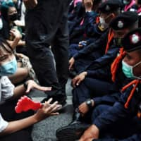 A young pro-democracy protester talks with police during a demonstration at an intersection in Bangkok on Thursday.  | AFP-JIJI