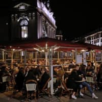 People enjoy a meal in Lille, northern France, on Friday ahead of new curfew that went into effect for the next month to slow the spread of COVID-19. | AP