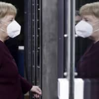 German Chancellor Angela Merkel is reflected in the glass of a door as she arrives for an EU summit in Brussels on Friday.   POOL / VIA AP