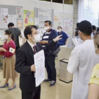 Residents of Tokyo's Shinagawa Ward complete procedures relating to their My Number cards in May. | KYODO