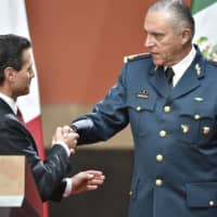 Mexican Defense Minister Salvador Cienfuegos (right) is congratulated by President Enrique Pena Nieto after a speech in Mexico City in January 2016. | AFP-JIJI