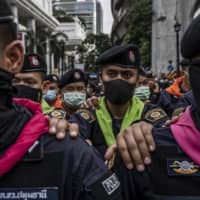 Royal Thai Police link arms to stop anti-government protesters during a protest at  Ratchaprasong intersection in the commercial center of Bangkok on Thursday.  | ADAM DEAN/THE NEW YORK TIMES