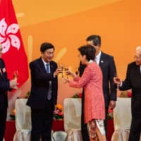 Carrie Lam (center), Hong Kong's chief executive, shares a toast with Luo Huining, director of the Liaison Office of the Central People's Government. | BLOOMBERG
