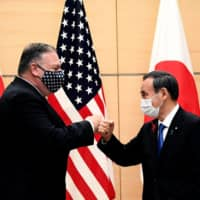 Prime Minister Yoshihide Suga and U.S. Secretary of State Mike Pompeo bump fists as they meet at the Prime Minister's Office in Tokyo on Oct. 6. | POOL / VIA AFP-JIJI