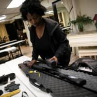 Andreyah Garland displays her shotgun before a training session. The U.S. gun market is widening this year to include a new rush of first-time buyers, including many women, minorities and politically liberal buyers who once would not have considered gun ownership. | REUTERS