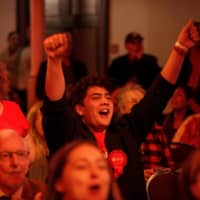 Supporters cheer as they watch the results come in during the New Zealand Labour Party's election night event in Auckland. | AAP IMAGE / VIA REUTERS