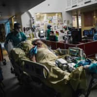 Medical workers transport a patient in the intensive care unit of Lariboisiere Hospital in Paris on Wednesday.    AFP-JIJI