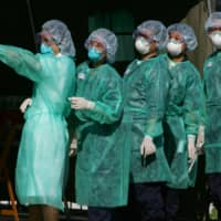 Health workers participate in a SARS outbreak drill in Hong Kong in 2004.    REUTERS