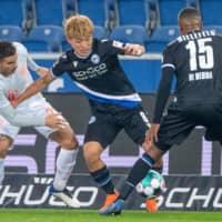 Arminia's Ritsu Doan (center) protects the ball from a Bayern player on Saturday in Bielefeld, Germany. | KYODO