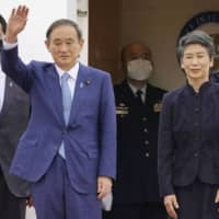 Prime Minister Yoshihide Suga and his wife, Mariko, leave on a trip to Vietnam and Indonesia from Haneda Airport in Tokyo on Sunday. | KYODO