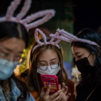A group of young girls wearing rabbit's ears look at a smartphone in Beijing on Friday. | AFP-JIJI