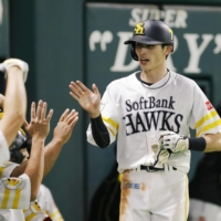 The Hawks' Ukyo Shuto is congratulated by his teammates after scoring against the Eagles during the eighth inning on Sunday in Fukuoka. | KYODO