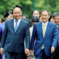Prime Minister Yoshihide Suga and his Vietnamese counterpart, Nguyen Xuan Phuc, walk at the Presidential Palace in Hanoi on Monday. | POOL / VIA REUTERS