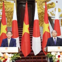 Prime Minister Yoshihide Suga and his Vietnamese counterpart, Nguyen Xuan Phuc, hold a joint news conference in Hanoi on Monday. | POOL / VIA KYODO