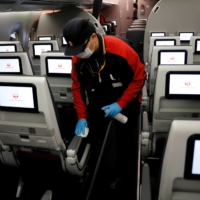 A Japan Airlines staff member cleans the cabin of a plane at Haneda Airport in May.  | REUTERS
