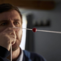 Mark Lenzi uses a Brock string for vision therapy at his home in Durham, New Hampshire. Lenzi, who worked for the State Department in Guangzhou, China, experiences the same mysterious affliction as dozens of staff members at the American Embassy in Havana. | CODY O'LOUGHLIN / THE NEW YORK TIMES