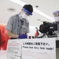 An official checks quarantine forms for passengers arriving at Narita Airport last month.   KYODO