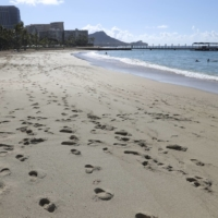 A near-empty Waikiki Beach is viewed on Thursday in Honolulu. A new travel testing program allows visitors from Japan who test negative for COVID-19 to come to Hawaii and avoid two weeks of mandatory quarantine. | AP