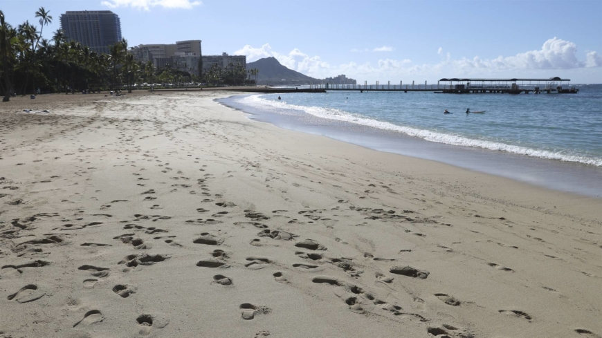 A near-empty Waikiki Beach is viewed on Thursday in Honolulu. A new travel testing program allows visitors from Japan who test negative for COVID-19 to come to Hawaii and avoid two weeks of mandatory quarantine.