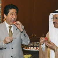 Then-Prime Minister Shinzo Abe eats strawberries grown in Tochigi Prefecture during an economic forum in Abu Dhabi in April 2018. | KYODO