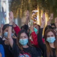 Pro-democracy activists flash three-fingered salutes while listening to the national anthem outside of the Siam Paragon shopping mall in Bangkok on Tuesday. | AP