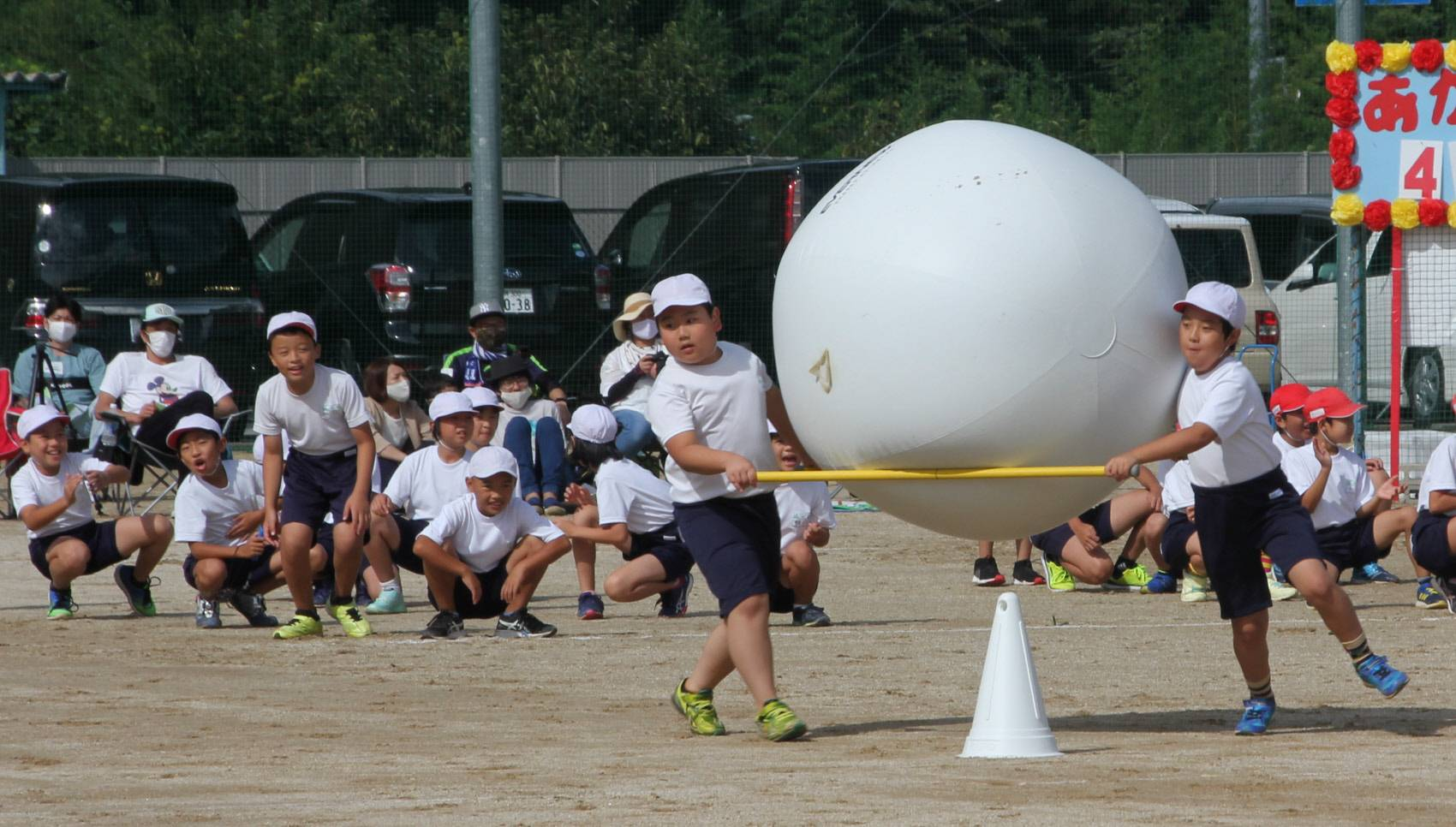 Students in Gero, Gifu Prefecture, participate in a race during sports day in September, holding two sticks to carry a big ball instead of rolling it with their hands.   CHUNICHI SHIMBUN