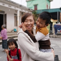 Jiho Yoshimizu, head of Japan Vietnam Mutual Support Association, hugs a child in Vietnam in February during her visit to the home of one of two former Vietnamese technical interns who died of accidental carbon monoxide intoxication in Tokyo in September 2019. | COURTESY OF JIHO YOSHIMIZU