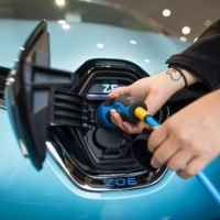 An employee places the electric charger into a new Renault Zoe automobile at a dealership in Lincoln, England, on Wednesday. | BLOOMBERG