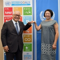 Liberal Democratic Party Upper House member Keizo Takemi (left) and Director of the United Nations Information Centre Kaoru Nemoto bump fists after their discussion in September. | YOSHIAKI MIURA
