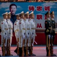 Military personnel stand in formation next to a portrait of Chinese President Xi Jinping outside the Forbidden City in Beijing on Thursday, on the eve of the 70th anniversary of China's entry into the 1950-53 Korean War. | AFP-JIJI