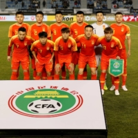 China's men's team poses for photos before their EAFF E-1 Football Championship match against Japan on Dec. 10 in Busan, South Korea. | REUTERS