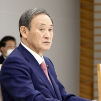 Prime Minister Yoshihide Suga attends a ministerial meeting at the Prime Minister's Office on Friday. | KYODO
