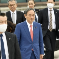 Prime Minister Yoshihide Suga is pictured at Noi Bai International Airport in Hanoi on Tuesday, before flying to Indonesia on the final leg of his two-nation Asia tour. | KYODO
