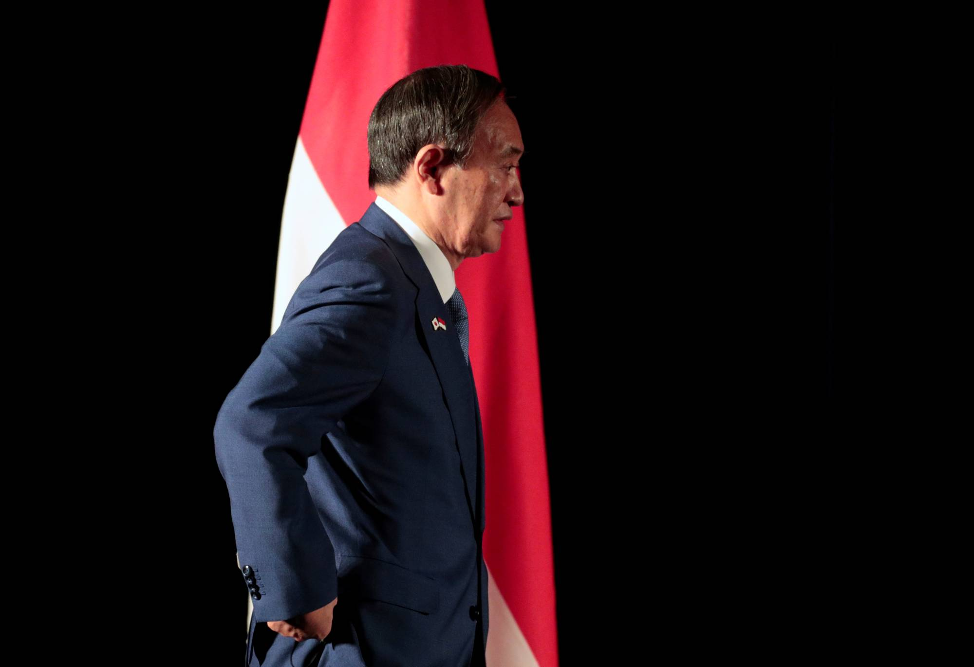 Prime Minister Yoshihide Suga walks past the Indonesian national flag as he arrives for a news conference in Jakarta on Wednesday. | POOL / VIA REUTERS
