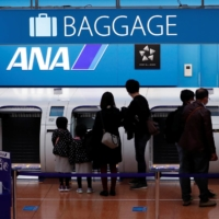 Passengers deposit their baggage at a check-in counter of All Nippon Airways at Haneda Airport in Tokyo on Friday. | REUTERS