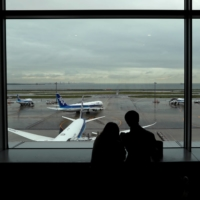 A couple watches ANA aircraft at Haneda Airport in Tokyo on Friday. | REUTERS