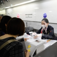 A Japan Airlines Co. employee assists passengers at Narita Airport in Chiba Prefecture on Sept. 26. | BLOOMBERG
