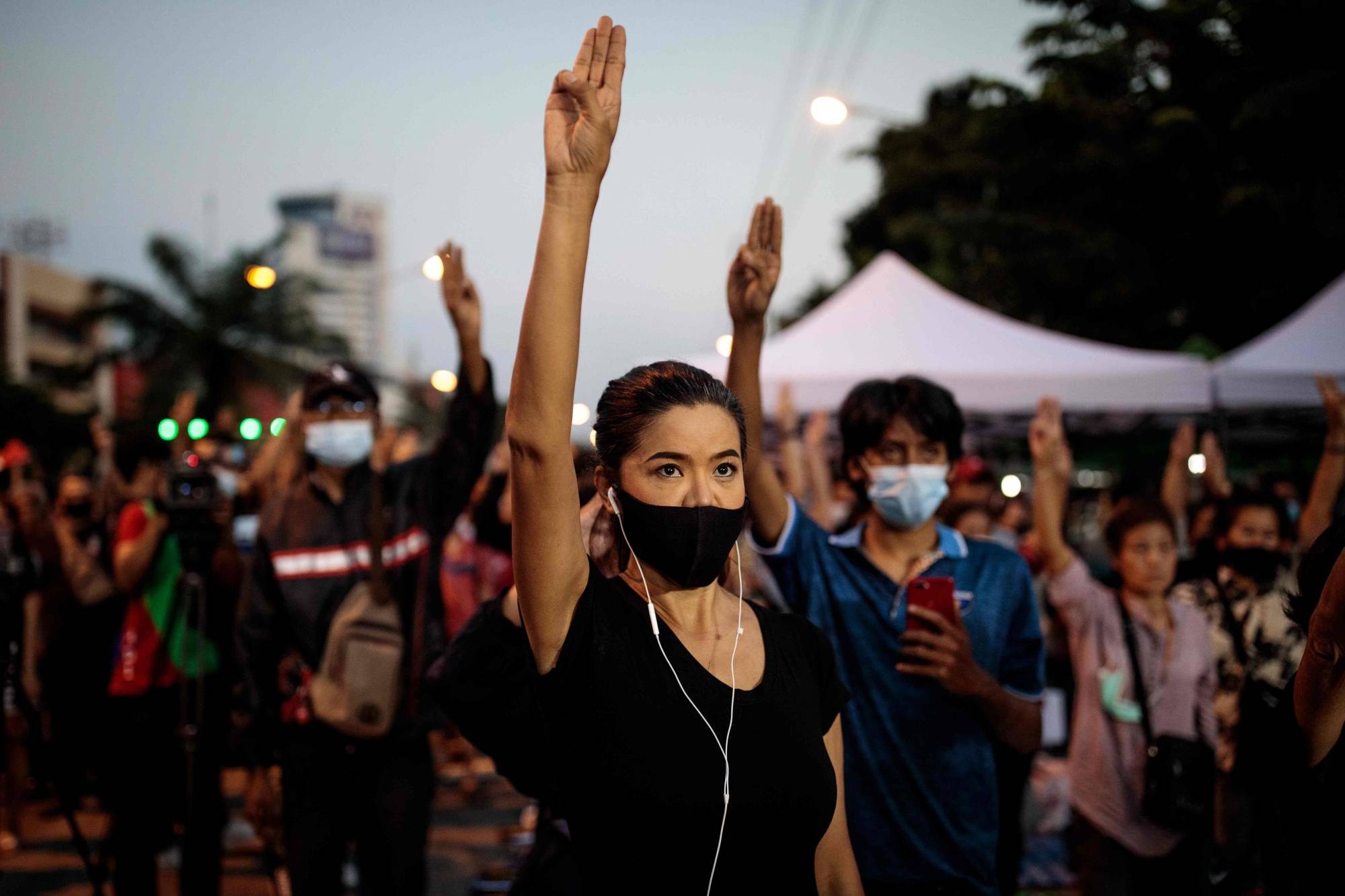 Pro-democracy protesters hold up the three-finger salute outside Bangkok Remand Prison on Saturday.  | AFP-JIJI