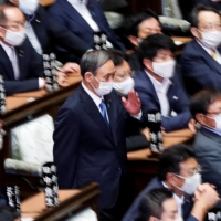 Yoshihide Suga, then chief Cabinet secretary, prepares to cast a vote to elect the new prime minister in the Diet's Lower House on Sept. 16. Now prime minister, Suga will speak before the Diet on Monday as it opens an extraordinary session.  | REUTERS