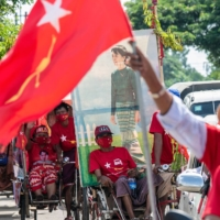 Supporters of the National League for Democracy party take part in a campaign event with a portrait of Myanmar State Counselor Aung San Suu Kyi in Yangon on Sunday. | AFP-JIJI