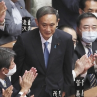 Yoshihide Suga is applauded in the Lower House of the Diet after being elected prime minister on Sept. 16. | AP