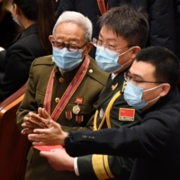 A veteran arrives in Beijing's Great Hall of the People for a ceremony marking the 70th anniversary of China's entry into the Korean War on Friday. | AFP-JIJI