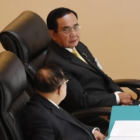 Tha Prime Minister Prayut Chan-ocha (top) talks to Deputy Prime Minister Prawit Wongsuwan during a special session at the parliament in Bangkok on Monday. | AP