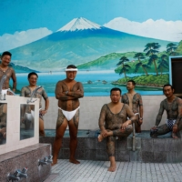 Tattoo artist Asakusa Horikazu poses for a photograph with people who received tattoos from Horikazu and his father, at a Japanese public bath in Tokyo on Sept. 24. | REUTERS